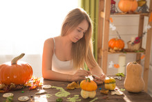 Ready To Halloween Invasion. Smiling Young Woman Covering Cookies And Pumpkin In Halloween Decorated Kitchen