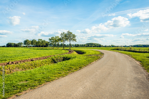 Foto  Curved country road in a Dutch polder landscape