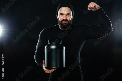 Happy and healthy muscular young fitness sports man with a jar of sports nutriti Fototapeta