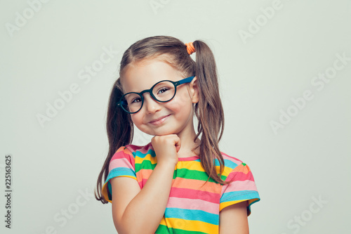 beautiful cute little girl posing and smiling to camera with her hand under chin