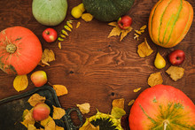 Thanksgiving Day Composition Of Vegetables, Sunflower, Apple And Fall Leaves On Wooden Background. Flat Lay, Top View. Autumn Dinner Table