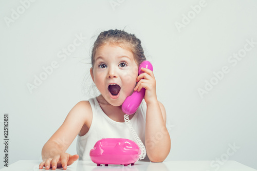 Carta da parati beautiful cute little girl talking on toy telephone with very excited expression