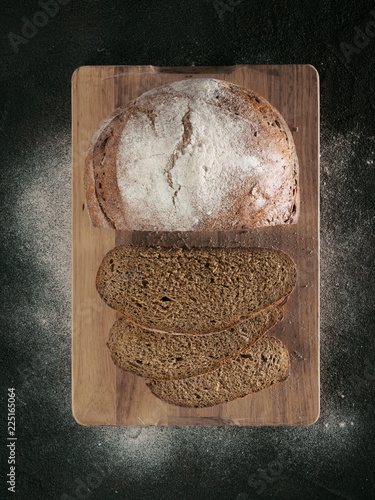 Fotografie, Obraz  Sliced homemade sourdough rye bread on cutting board over black textured background with rye flour