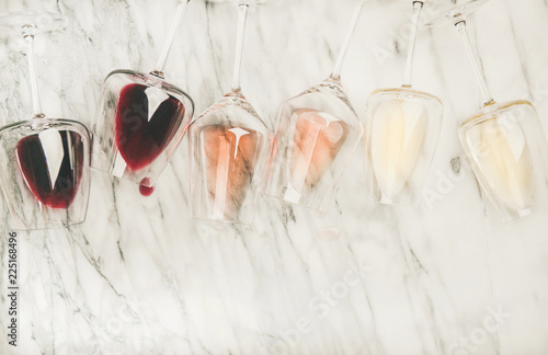Flat-lay of red, rose and white wine in glasses and corkscrews over grey marble background, top view, copy space. Bojole nouveau, wine bar, winery, wine degustation concept