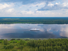 Aerial View Of River Volga And Cruise Ship Sailing Along. Green Riversides And Cloudy Sky. Summer Photo From Drone, Russia