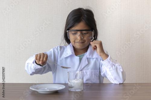 Fotografia  Cute little girl scientist conducting an experiment