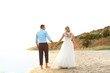 Wedding couple holding hands together on beach
