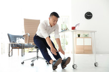 Young Businessman Stretching In Office. Workplace Fitness