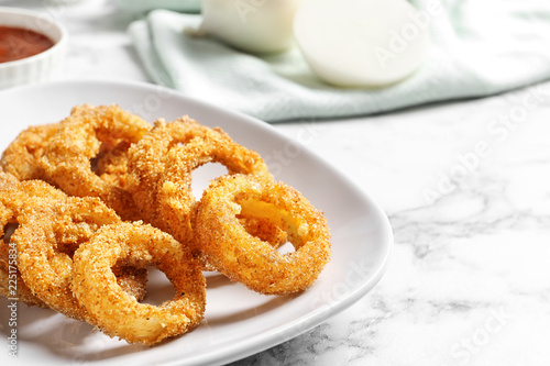 Plate with homemade crunchy fried onion rings on marble table, closeup. Space for text