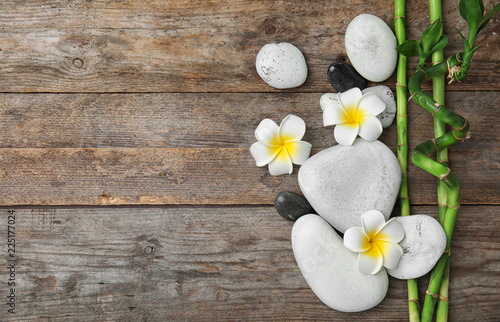 Staande foto Spa Flat lay composition with bamboo branches and spa stones on wooden background. Space for text