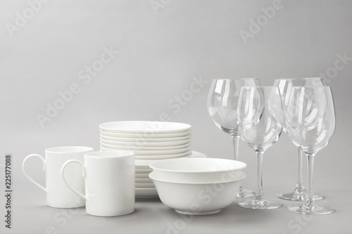 Set of clean tableware on grey background. Washing dishes