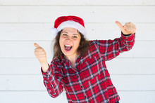 Christmas And People Concept - Cheerful Young Woman In Christmas Hat Showing Thumbs Up On White Background