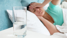 Closeup Image Of Glass Of Water Against Woman With Headache Lying In Bed