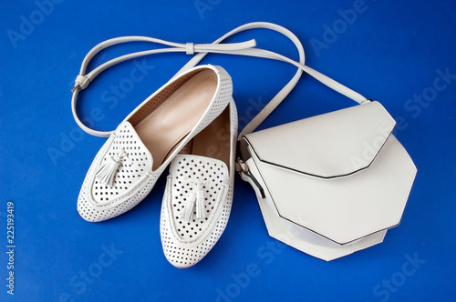 white leather modern shoes and bag on blue background, cute ladies bag and  shoes, flat, top view. Spot shoes and casual shoes, sales