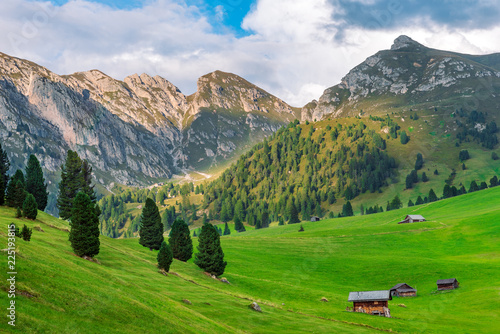 alpine fields and village house in St. Maddalena in Dolomites before sunset