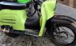 Grüner Motorroller auf grauem Kopfsteinpflaster