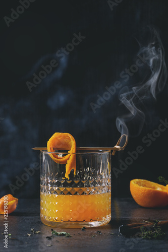 Glass of Scotch Whiskey orange juice alcohol cocktail with swirled orange peel on skewer, thyme and smoking cinnamon sticks standing on black marble table.