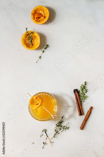 Glass of Scotch Whiskey orange juice alcohol cocktail with swirled orange peel on skewer tyme herbs and cinnamon sticks standing on white marble background. Flat lay, space