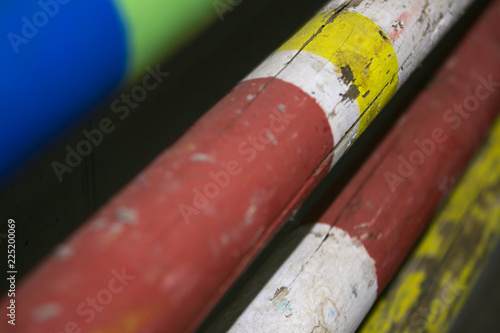 Stack of equestrian jumping poles in various colors