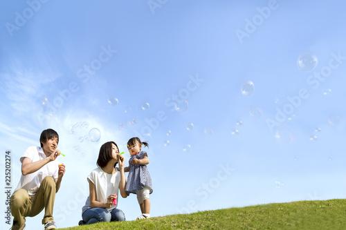 Valokuva  公園で青空バックにシャボン玉をして遊ぶ幸せな親子。家族、親子、幸せ、愛情、育児、健康イメージ