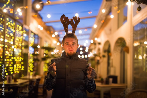 Fotografia, Obraz  People, holidays and christmas concept - surprised man in deer's horns holding t