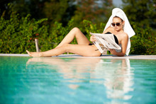 Beautiful Young Woman With Towel On Her Hair Reading Newspaper Near Hotel Pool