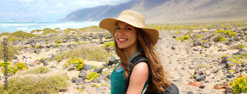 In de dag Canarische Eilanden Happy beautiful traveler girl with straw hat looking to the camera. Young female backpacker exploring Lanzarote, Canary Islands. Banner panorama.