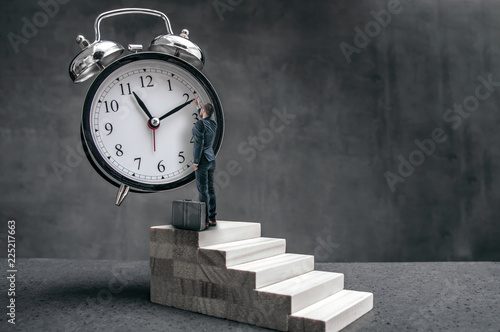 Fotografía Businessman stands on stairs and tries to change clock hand position