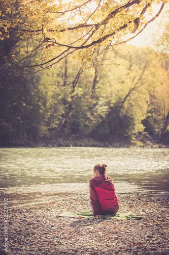 Foto  Junge Frau sitzt am Ufer eines Flusses und genießt die Sonne, Hinteransicht