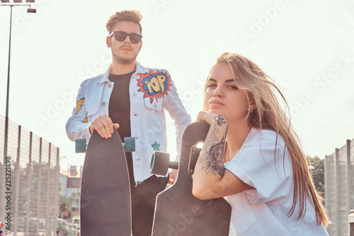 Fotografie, Obraz  Close-up portrait of young trendy dressed hipster couple with skateboards posing