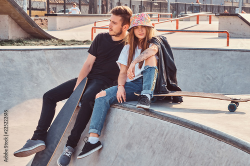 Young hipster couple trendy dressed relaxing together with skateboards on a skatepark on a sunny day.