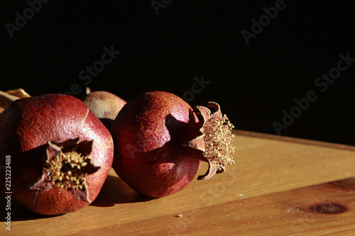 Fotografía  Still life with Couple of Dry Pomegranates on the wooden table,