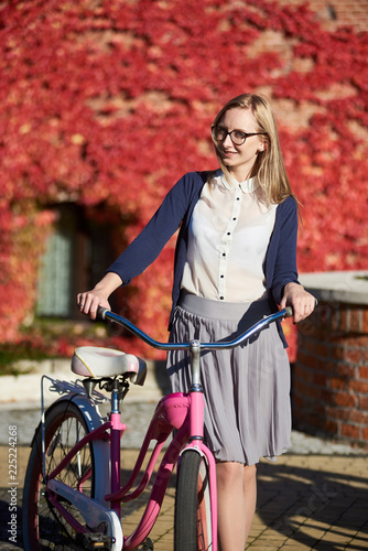 Fotografia  Young pretty long-haired smiling blond woman in casual clothing and glasses with pink lady bicycle on bright warm sunny day on background of brick wall overgrown with beautiful red ivy leaves