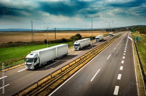 Caravan or convoy of White Lorry  trucks in line on a country highway Canvas Print