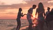 Friends dancing on the beach. Sunset time.