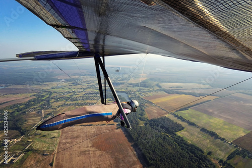 Photo of brave extreme hang glider pilot flying high and fast above terrain