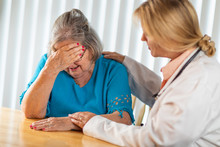 Female Doctor Consoling Distraught Senior Adult Woman