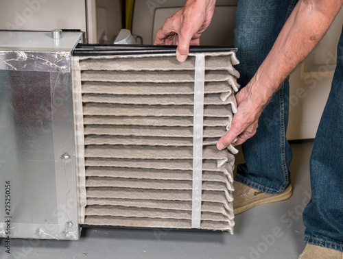 Fotografia, Obraz  Senior man changing a dirty air filter in a HVAC Furnace