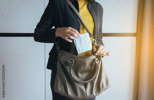 Fotografia  Woman hand putting sanitary napkins in handbag,White menstrual pad