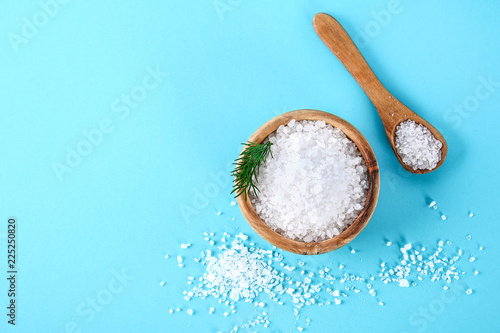 Crystals of large sea salt in a wooden bowl and spoon and dill on a blue table Canvas