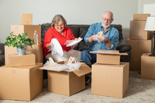 Senior Adult Couple Packing Or Unpacking Moving Boxes