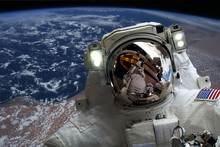 Astronaut Flying In Outer Space Near Planet Earth Doing Some Work Near Space Ship, Elements Of This Image Were Taken From NASA Photos F