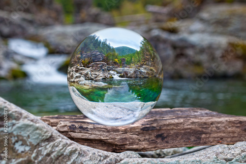 Fotografie, Obraz  Crystal glass ball sphere reveals nature landscape with macro view