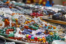 Many Strings Of Colorful Beads Made Of Natural Stones On The Counter In The Market