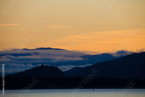 Silhouetted hills around Shuswap Lake and colorful orange sky, British Columbia, Canada