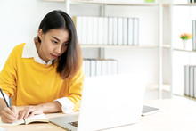 Young Attractive Asian Female Student Sitting At Table Looking At Laptop Writing Journal By Hand Note Idea Script, Diary Or Sketch Design On Notebook At Home Office Or Library With Copyspace Concept.