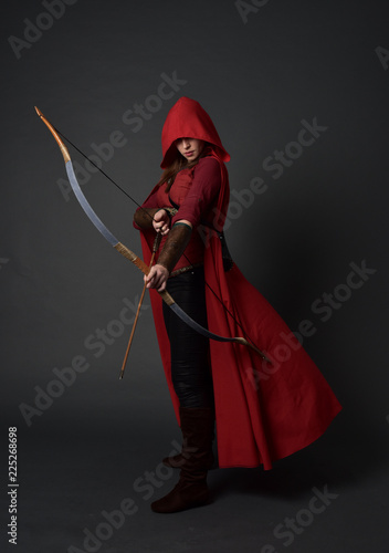 Foto full length portrait of brunette girl wearing red medieval costume and cloak, holding a bow and arrow