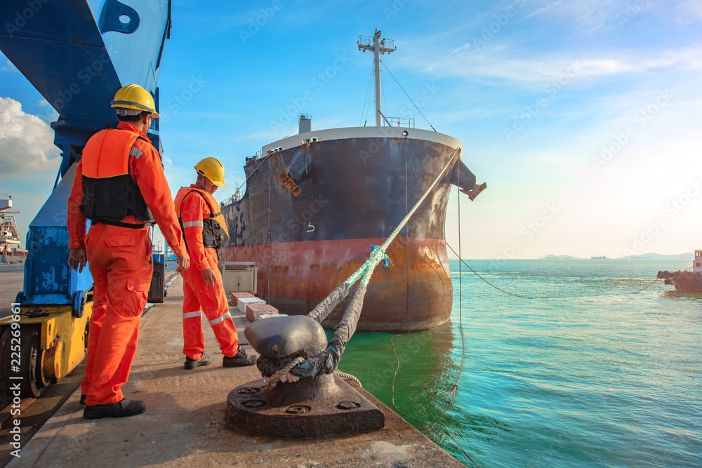 Fototapety, obrazy: ship vessel is on leaving departure from the port terminal after completion of loading/discharging operation by gang of mooring attending at last party, tug boat standing by to safety assist towage