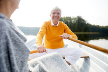 Cheerful Excited Handsome Elderly Man In Shirt And Yellow Sweater Sitting On Boat And Rowing With Oars While Talking To Woman