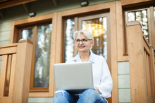Smiling Modern Working Senior Lady In Glasses Sitting On Porch Of Cottage And Looking Into Distance While Working On Project Using Laptop